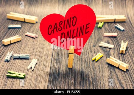 Wort schreiben Text Casino Online. Business Konzept für Computer Poker Spiel Spielen Royal Wette Lotto High Stakes Clothespin halten roten Herz aus Papier severa - Stockfoto