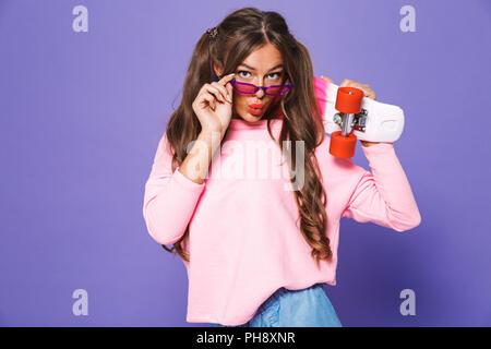 Porträt einer positiven Mädchen sweatshirt mit Skateboard über violett Hintergrund posiert - Stockfoto