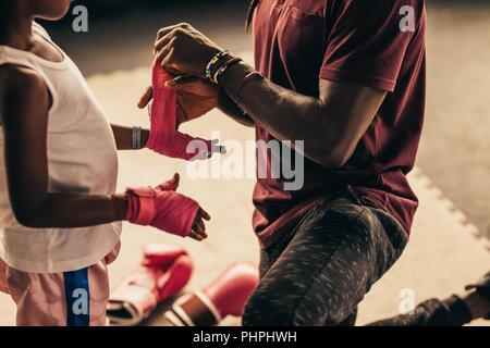 Boxtrainer Verpackung Verband auf Hände und Finger von ein Kind vor dem Anziehen von Boxhandschuhen. - Stockfoto