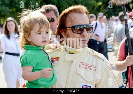 Emerson Fittipaldi mit enkeltochter am Goodwood Festival der Geschwindigkeit im Rennen Overalls. Die brasilianische Automobilindustrie Rennfahrer, Formel 1 und Indy 500 - Stockfoto