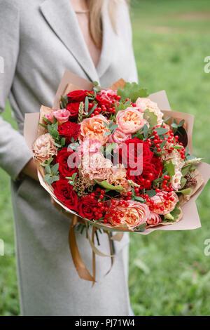 Schöne Frau mit einem schönen Herbst Bouquet. Blumenarrangement mit Nelken und Rote Garten Rosen. Farbe pink. grünen Rasen im Hintergrund - Stockfoto