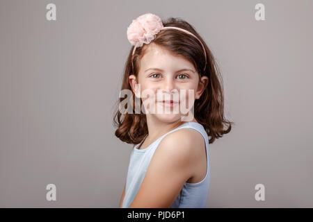 Closeup Portrait von cute adorable White brunette Kaukasischen Vorschule Mädchen, die Gesichter vor der Kamera. Kind lächelnd lachend im Studio auf - Stockfoto