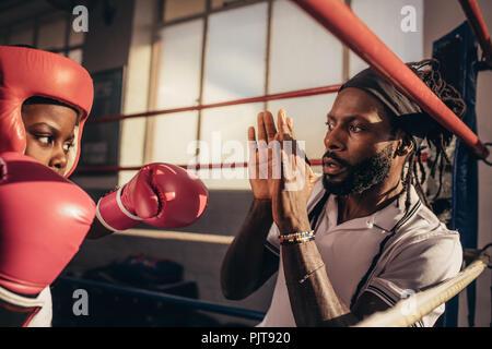 Nahaufnahme eines Boxen kid Training mit seinem Trainer in einem Boxring. Kind üben Schläge auf die Hände von seinem Trainer. - Stockfoto