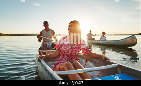 Lächelnden jungen Frau Kanu mit ihrem Freund und Freunden auf einen stillen See am späten Nachmittag - Stockfoto