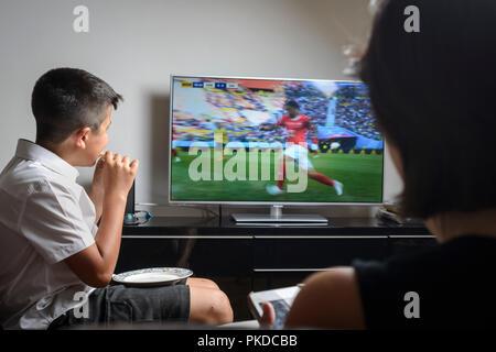 Schüler, die 10 Jahre alt, in Schuluniform Snacking und beobachten Fußballspiel im Fernsehen - Stockfoto