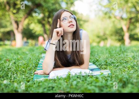 Junge Frau mit Buch im Park. Ernsthafte schöne Mädchen liegt auf Gras beim Lesen lieblings Romantik. - Stockfoto