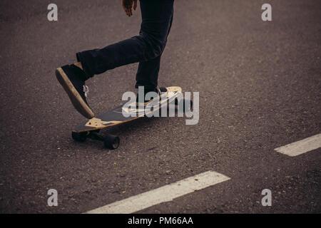 7/8 männliche Teenager skateboarding in der Stadt mit einem Fuß an Bord - Stockfoto