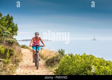 Kroatien, Pula, Kap Kamenjak, Mountainbiker an der Küste - Stockfoto
