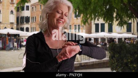 Gesunde reife Jogger prüft Ihre Herzfrequenz nach in der Stadt laufen - Stockfoto