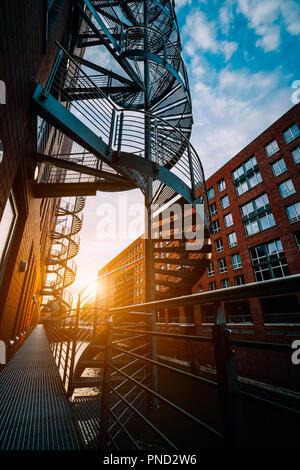 Wendeltreppen in der Speicherstadt. Schmalen Kanal und roten Backsteinbauten der Speicherstadt in Hamburg im warmen Abendlicht. Low Angle Shot - Stockfoto