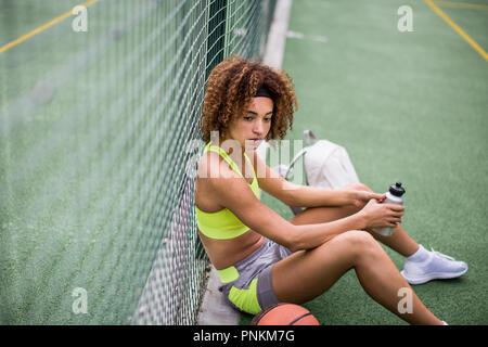 Junge erwachsene Frau sitzt auf einem Basketballplatz - Stockfoto
