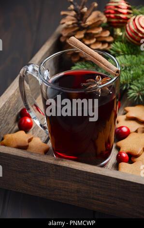 Weihnachten Glühwein. Urlaub Konzept mit Tannenzweigen geschmückt, Gingerbread Cookies und Preiselbeeren auf dunklen Holz- Fach. - Stockfoto