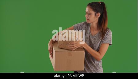 Lässige junge Frau, die Durchführung von Versandkartons auf Green Screen - Stockfoto