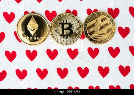 Gold physischen Bitcoin, Litecoin und des Astraleums Münzen auf rotes Herz Hintergrund. Crypto Währung Markt Liebe abstraktes Konzept. Kopieren Platz an der Unterseite. Fl - Stockfoto