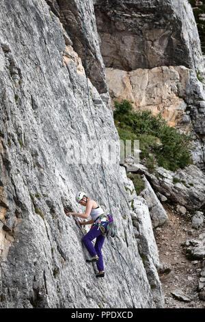 Cortina d'Ampezzo, Italien - 17. August 2018: ein Bergsteiger klettert mit seinen Händen, die auf einer felsigen Wand. Lage Cinque Torri, Dolomiten. - Stockfoto