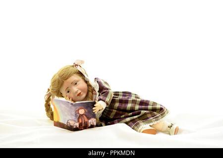 Puppe Elise (Kopf 109 von Kaemmer & Reinhardt, Jahr 1909) liegst liegend ein Buch (Puppe Elise liegt und liest ein Buch) - Stockfoto