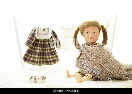 Puppe Elise (Kopf 109 von Kaemmer & Reinhard, Jahr 1909) hat Wäsche gewaschen und sie zum Consider auf eine Wäscheleine gehängt - Stockfoto