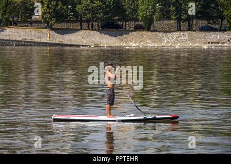 Person auf einem Paddle Board an der Moldau im Zentrum von Prag, ein Foto. - Stockfoto