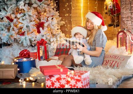 Mutter mit Baby in einen Hut von Santa Claus in der Weihnachtszeit. - Stockfoto