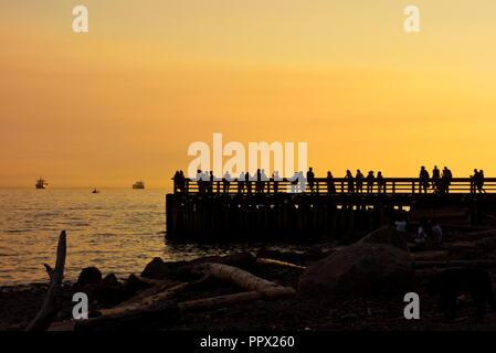 Silhouetten von Menschen auf der Pier bei Sonnenuntergang in Ambleside in West Vancouver, BC, Kanada. - Stockfoto