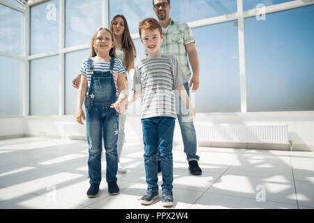 Bruder und Schwester mit ihren Eltern in ein geräumiges Apartment stehend - Stockfoto