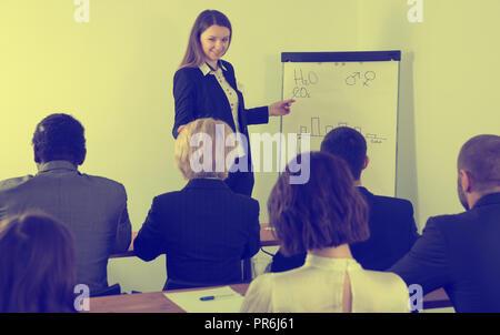Junge Geschäftsfrau eine Präsentation halten zu internationalen Partnern bei der Sitzung - Stockfoto