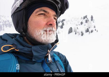 Alter Mann mit weißem Bart gefroren auf verschneiten Berg mit Ski Googles und Helm, Porträt, auf Distanz beobachten, kalten Winter. - Stockfoto