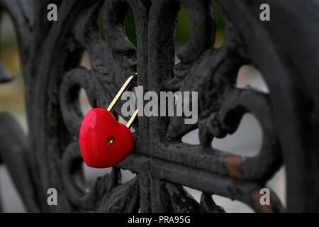 Leuchtend rote geschlossenen Vorhängeschloss in der Form eines Herzens auf einem schwarzen alten Geländer der Brücke, liebe Symbol - Stockfoto