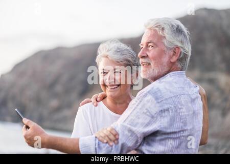 Konzept der Ferienhäuser, Technologie, Tourismus, Reisen und Menschen - gerne älteres Paar mit Handy Telefon auf Pebble Beach Lachen und Scherzen umarmen ein - Stockfoto