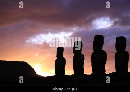 Atemberaubende Purple Sunrise bewölkter Himmel über der Silhouette des riesigen Moai Statuen von Ahu Tongariki Archäologische Stätte, Easter Island, Chile - Stockfoto