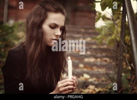 Brunette Goth Girl mit einer Kerze in der Hand im Wald - Stockfoto