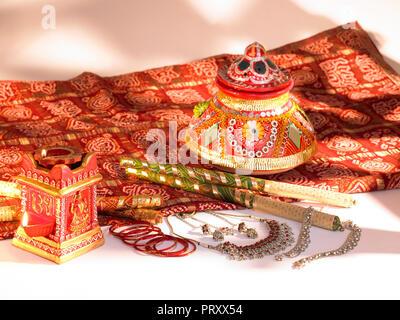 Ein Stilleben von DASSERA FESTIVAL OBJEKTE IN MUMBAI INDIEN ZEIGEN EINE KALASH/POT, DIYAS, Süßigkeiten, BANDHANI, SAREE, SILBER THALI mit Kokosnuss, DIYA, Blume - Stockfoto