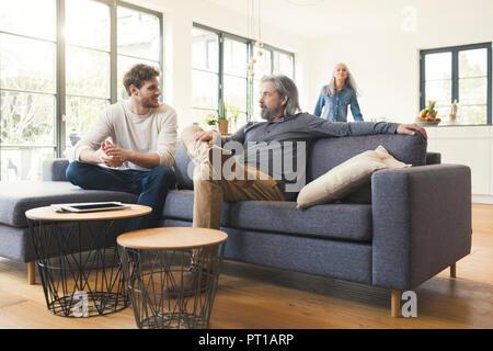 Sohn sitzen auf der Couch, im Gespräch mit seinem Vater - Stockfoto