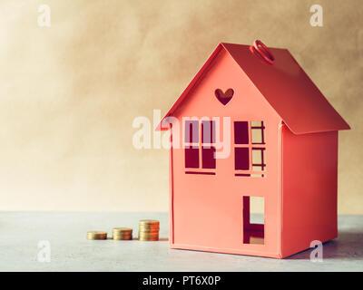 Metall rot Modell eines Hauses und Treppen von Goldmünzen. Das Konzept der Anmietung oder Kauf der Immobilien. - Stockfoto