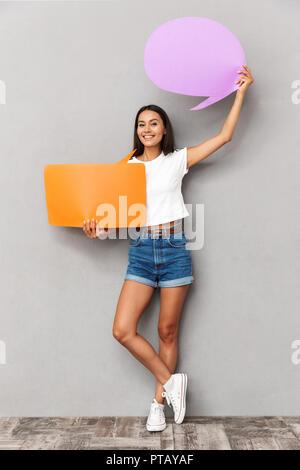 Fröhliche Frau legere Kleidung halten zwei leere Blasen mit Copyspace über grauer Hintergrund - Stockfoto