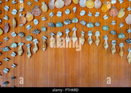 Sommer Konzept Hintergrund mit Muscheln Mobile zum Aufhängen auf braunem Holz. - Stockfoto