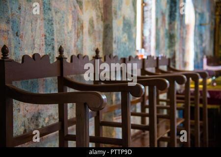 Hohe Stühle aus Holz in der griechischen Kirche - Stockfoto