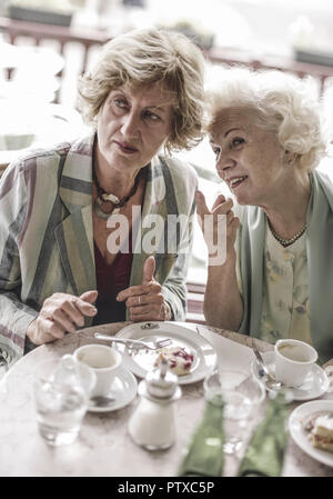 Zwei Seniorinnen einer im Strassencafe, Beobachten Etwas (Model-Release) - Stockfoto