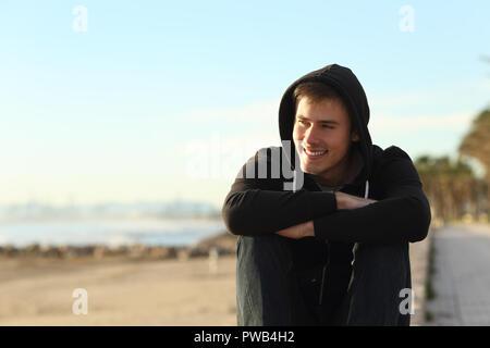 Vorderansicht Porträt eines Teenager-Jungen sitzen am Strand entfernt suchen - Stockfoto