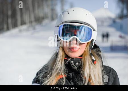 Junge erwachsene Frau Snowboarder oder Skifahrer Nahaufnahme portrait tragen weiße healmet mit Maske im Schnee Winter Berg - Stockfoto