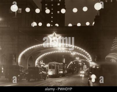 Weihnachten in den 1930er Jahren. Die belebte Straße Kungsgatan mit Weihnachtsbeleuchtung dekoriert ist. Die Straßenbahn und die Autos fahren Sie unter einer der Brücken auf der Straße. Schweden 1930 - Stockfoto