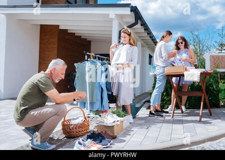 Vier Mitglieder der glücklichen Familie Gefühl fröhlichen beim Besuch Wochenende Yard Sale - Stockfoto