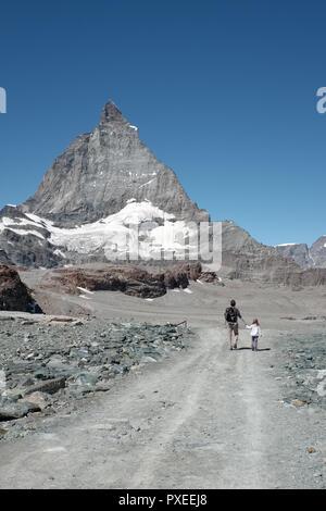 Vater und Kind Wandern in den Schweizer Alpen mit Blick auf das Matterhorn im Hintergrund, Montag, 22. August 2016, in der Nähe von Zermatt, Schweiz. - Stockfoto