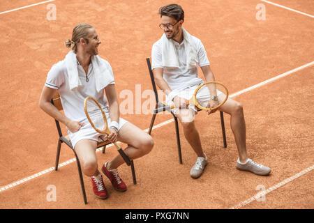 Tennis Spieler mit Handtüchern und Holz- Schläger ruhen auf Stühlen auf braun Hof - Stockfoto