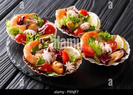 Schönen Seafood cocktail Salat von Garnelen, Tintenfische, Muscheln, Tintenfische und Jakobsmuscheln mit Gemüse in Muscheln close-up auf einem Schwarzen Tisch. horizo - Stockfoto