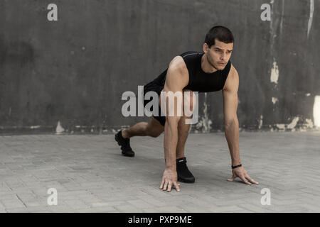 Sportler seinen Sprint auf grauem industrial Wand Hintergrund mit kopieren. Sport. Athlet Runner. - Stockfoto