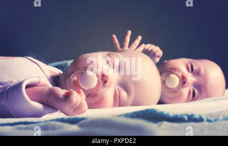Niedlichen neugeborenen Zwillinge Junge und Mädchen sind auf dem Bett liegend vor einem dunklen Hintergrund. Mit tonen und Unschärfen - Stockfoto