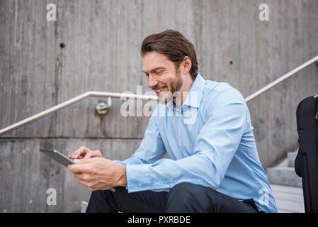 Lächelnd Geschäftsmann mit Koffer sitzen auf der Treppe mit Tablet - Stockfoto