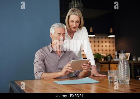 Älteres Ehepaar mit Tablette zu Hause - Stockfoto