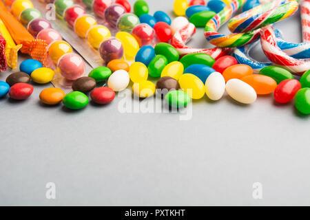 Verschiedene bunte Bonbons auf grauem Hintergrund, selektiver Fokus - Stockfoto